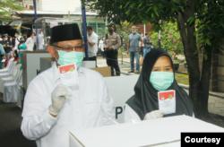 Akhyar Nasution bersama istrinya saat menunjukkan surat suara di Pilkada Medan, Rabu 9 Desember 2020, (courtesy- Tim Pemenangan Akhyar Nasution)