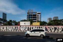 Sebuah mobil melewati tembok pinggir jalan penuh coretan di tengah pandemi COVID-19 di Jakarta, 21 Juni 2021. (Foto: BAY ISMOYO / AFP)
