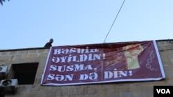 Qiyas İbrahimov binanın üzərində plakat qaldırarkən