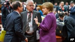 Thủ tướng Đức Angela Merkel (phải) nói chuyện với Tổng thống Pháp Francois Hollande (trái) tại hội nghị thượng đỉnh EU ở Brussels 15/3/13