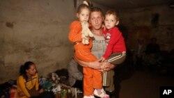 Seorang pria menggendong dua orang anaknya di dalam sebuah basement (ruang bawah tanah) untuk menghindari peperangan di Donetsk, Ukraina timur (foto: dok).