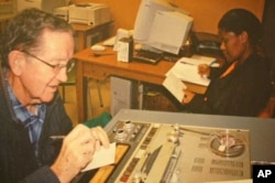 Ethnomusicologist Andrew Tracey (left) taking notes about one of his father's, Hugh Tracey's, tape recordings at the International Library of African Music