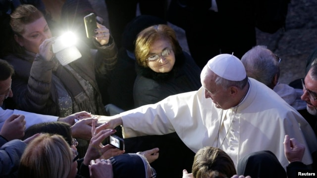 FILE - Pope Francis greets the faithful as he arrives to visit the Church of St Alfonso Maria dei Liguori in the outskirts of Rome, Jan. 6, 2014.