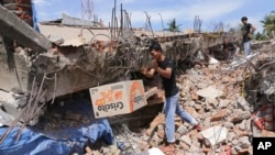 A man removes a box of food from under the rubble of a building that collapsed after an earthquake in Pidie Jaya, Aceh province, Indonesia, Dec. 7, 2016.