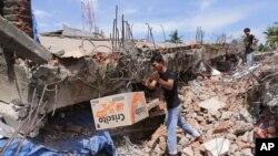 Seorang pria mengambil sebuah kotak makanan dari bawah reruntuhan bangunan pasca gempa yang menghantam wilayah Pidie Jaya, provinsi Aceh, Indonesia, 7 Desember 2016 (AP Photo/Heri Juanda).