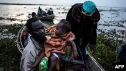 Des congolais embraquent dans des pirogues sur la rive du lac Albert fuient les violences interethniques à Tchomia, Ituri, RDC, 5 mars 2018.