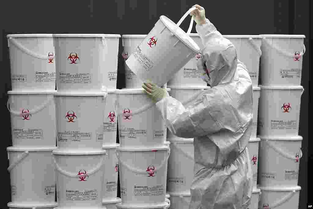 A worker in protective gear stacks plastic buckets containing medical waste from coronavirus patients at a medical center in Daegu, South Korea.