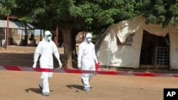 Health workers walk toward an area used for Ebola quarantine after they worked with Fanta Kone, 2, who died of the disease Friday at an Ebola virus center in Kayes, Mali.