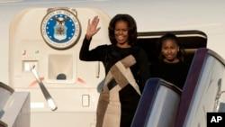 米歇尔到达北京下飞机时以美国华裔设计师林健诚(Derek Lam)的黑底拼图连衣裙和长筒紧身靴惊艳亮相