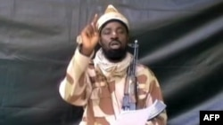 A grab made on July 13, 2013 from a video obtained by AFP shows the leader of the Islamist extremist group Boko Haram Abubakar Shekau, dressed in camouflage and holding an Kalashnikov AK-47.