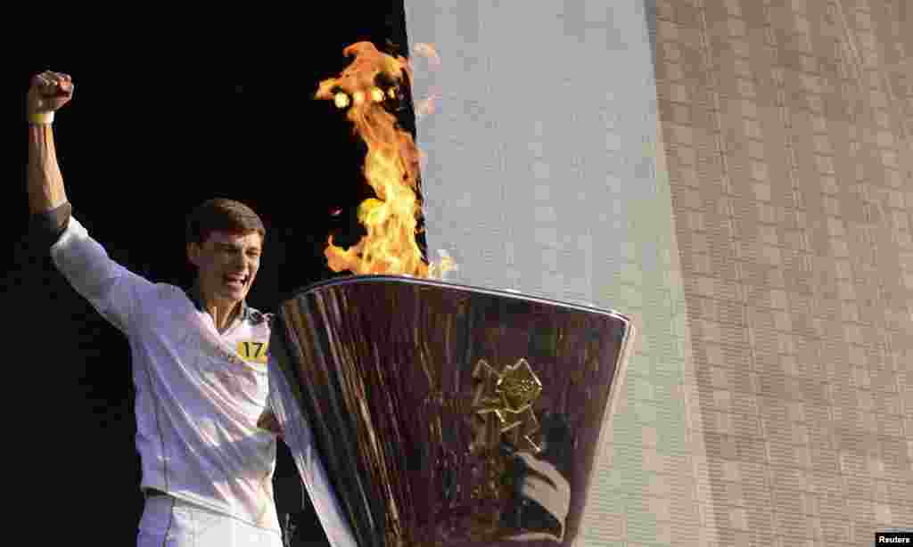 Torchbearer Tyler Rix lights the Olympic Cauldron during the Olympic torch relay celebrations in Hyde Park, London, July 26, 2012.
