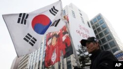 An anti-communist person holds a national flag during a rally to celebrate the victory of South Korea's president-elect Park Geun-hye of Saenuri Party in front of the party headquarters in Seoul, South Korea, December 20, 2012.