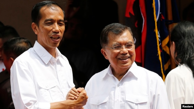 "Indonesian presidential candidate Joko ""Jokowi"" Widodo (L) and his vice presidential running mate Yusuf Kalla shake hands during an event declaring their bid in the upcoming July 9 election, in Jakarta, May 19, 2014."