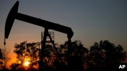 In this Feb. 19, 2015 photo, the sun sets behind an oil well in a field near El Tigre, a town within Venezuela's Hugo Chavez oil belt, formally known as the Orinoco Belt.