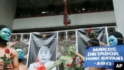 Mahasiswa Universitas Filipina memasang plakat dan berlarian tanpa mengenakan pakaian di kampus mereka sebagai bentuk aksi protes atas pemakaman mantan diktator Filipina, Ferdinand Marcos di Taman Makam Pahlawan, di kota Quezon, Filipina, 25 November 2016 (AP Photo/Bullit Marquez).