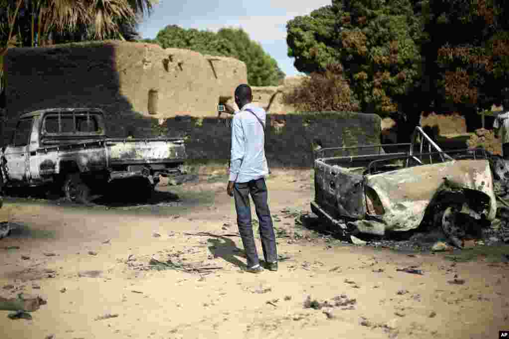 An unidentified man takes a picture of the charred remains of trucks used by radical Islamists on the outskirt of Diabaly, Mali, January 21, 2013.
