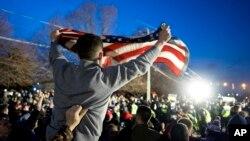 Pristalica Donalda Trampa maše američkom zastavom stojeći naspram grupe demonstranata protiv Trampa za vreme predizborne kampanje 2016, u Betpejdžu u državi Njujork.