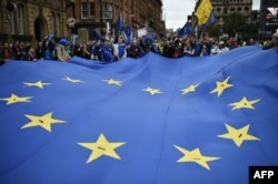 FILE - Protesters carry a giant EU flag during an anti-Brexit march in Manchester, Oct. 1, 2017.