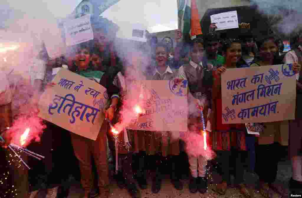 Students light firecrackers and hold placards to celebrate after India's Mars Orbiter successfully entered the red planet's orbit, at a school in the western Indian city of Ahmedabad, Sept. 24, 2014.