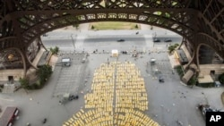 Thousands of people performed yoga on yellow mats at the Eiffel Tower in Paris Sunday.