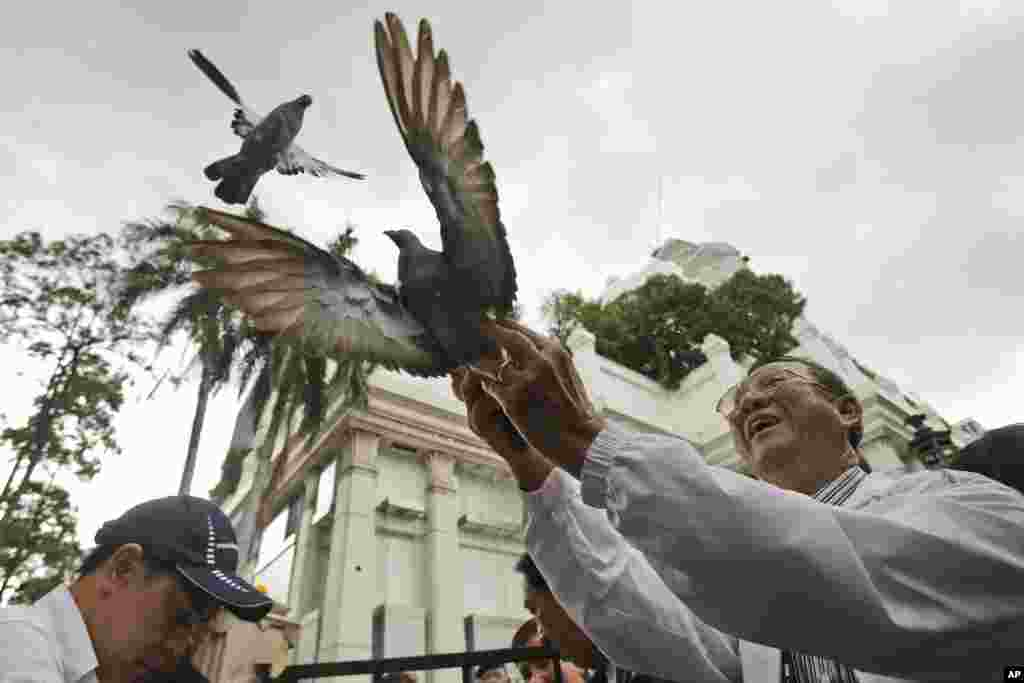 Doves are released for peace at the Erawan Shrine at Rajprasong intersection, the scene of Monday's bombing, in Bangkok, Thailand. Somber horns sounded Friday at the site of the deadly blast as officials joined a multi-religious ceremony for victims of the attack.