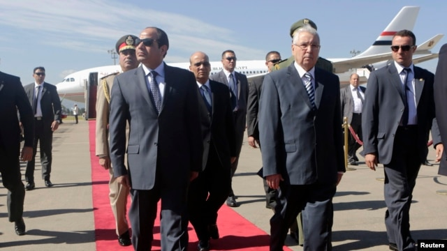 Egypt's President Abdel Fattah al-Sisi (L) walks with Algeria's Senate President Abdelkader Bensalah (R) upon his arrival at Algiers airport June 25, 2014.