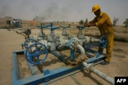 FILE - An Iraqi worker checks the valves at the Kirkuk oil field on June 29, 2009, 225 kms from Baghdad.