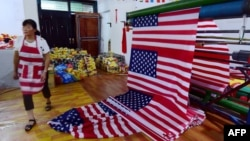 "A Chinese employee walks past newly made U.S. flags at a factory in Fuyang in China's eastern Anhui province, July 13, 2018. As the U.S.-China trade war rages, a factory set amid corn and mulberry fields in central China stitches together U.S. and ""Trump"