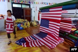 "A Chinese employee walks past newly made U.S. flags at a factory in Fuyang in China's eastern Anhui province, July 13, 2018. As the U.S.-China trade war rages, a factory set amid corn and mulberry fields in central China stitches together U.S. and ""Trump 2020"" flags."