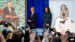 Former President Barack Obama and former first lady Michelle Obama stand on stage together as their official portraits are unveiled at a ceremony at the Smithsonian's National Portrait Gallery, Feb. 12, 2018, in Washington.