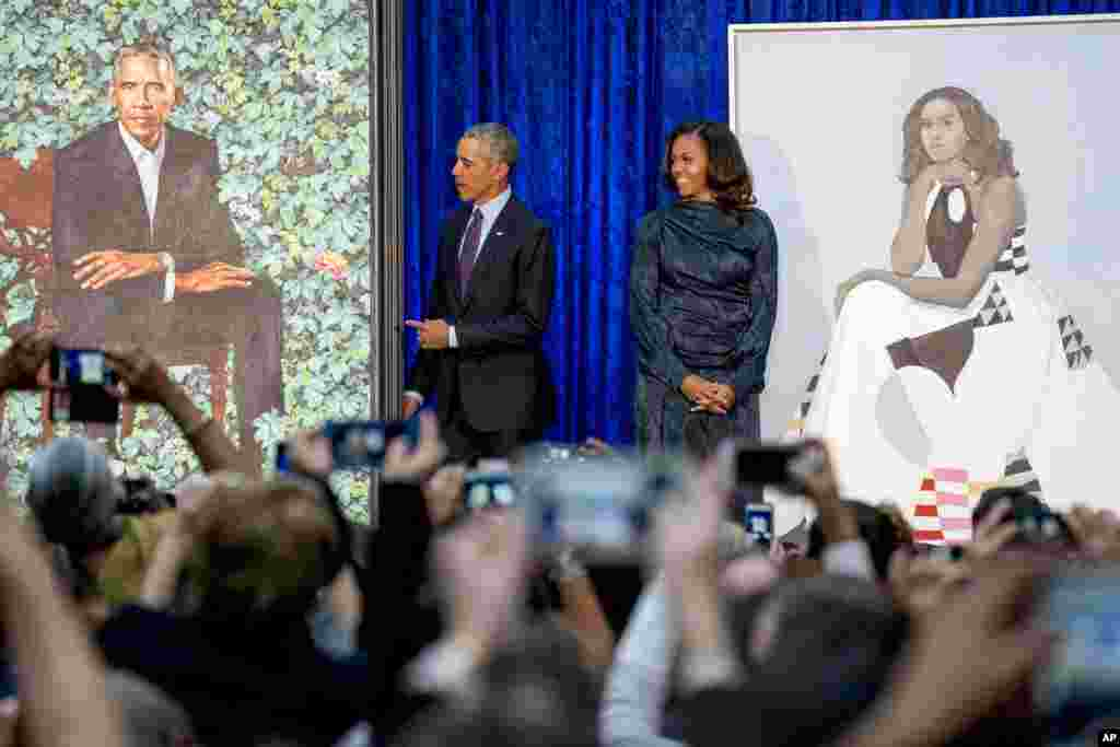Former President Barack Obama and former first lady Michelle Obama stand on stage together as their official portraits are unveiled at a ceremony at the Smithsonian's National Portrait Gallery in Washington, D.C.