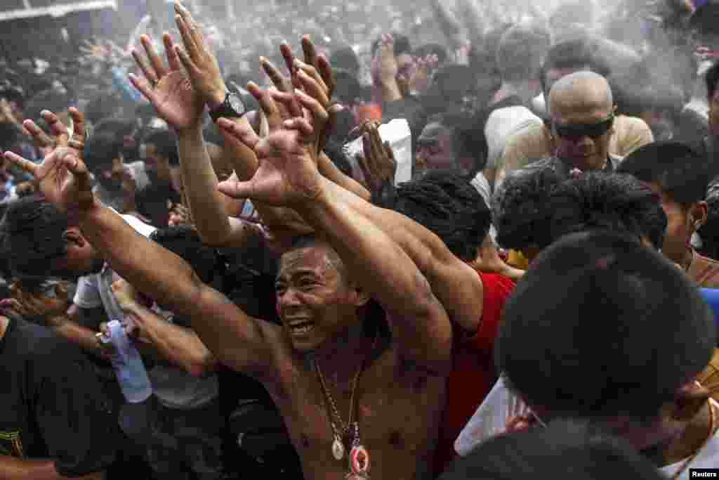 Các tín đồ mộ đạo đưa tay đón nhận nước thánh các nhà sư ban cho trong lễ hội hàng năm Magic Tattoo tại Wat Bang Phra ở tỉnh Nakhon Prathom, Thái Lan.