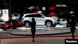 在纽约市举行的纽约国际汽车展上,车模们站在参展车辆边。(2014年4月16日)