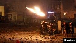 Para pengunjuk rasa pro-Eropa melemparkan bom ke arah polisi anti huru-hara saat terjadi bentrokan di Kyiv (20/1).