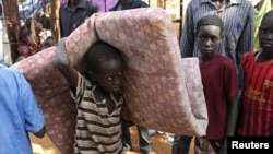 An internally displaced boy carries his belongings inside a United Nations Missions in a compound in Juba, South Sudan, Dec. 19, 2013.