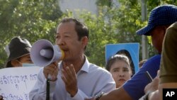 Rong Chhun, presiden Konfederasi Serikat Pekerja Kamboja, menggunakan megafon saat berlangsungnya aksi protes di dekat kediaman perdana menteri Hun Sen di Phnom Penh, 29 Juli 2020. (Foto: dok).