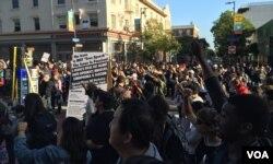 Đoàn biểu tình giơ tay hô to những khẩu hiệu phản đối chính sách của Tổng thống Trump. (Ảnh: Bùi Văn Phú)