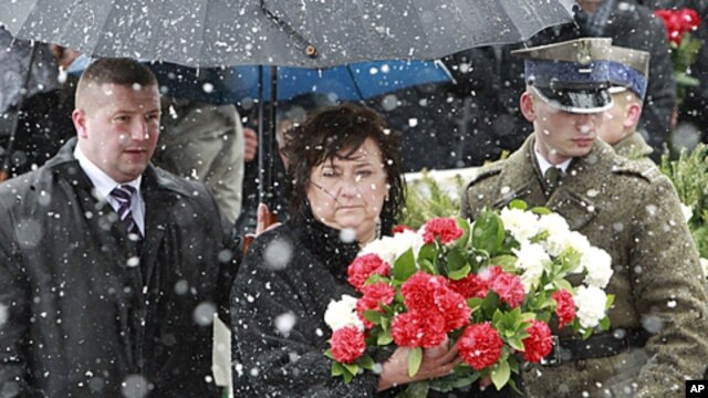 Poland's first lady Anna Komorowska (C) walks to lay flowers during a ceremony at the site of a plane crash that killed former Poland's President Lech Kaczynski and 95 others near the Russian city of Smolensk, April 9, 2011