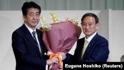 Japanski premijer Šinzo Abe i njegov naslednik Jošihide Suga posle izbora u Liberalno demokratskoj partiji