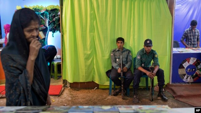"Bangladeshi policemen guard outside a shutdown stall of ""Badwip Prokshan,"" a publishing house at a major month-long book fair in Dhaka, Bangladesh, Feb.16, 2016."