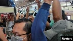Para penumpang, sebagian besar mengenakan masker, tampak berdesakan di dalam kereta di Jakarta, hari Senin (23/3) di tengah perebakan virus corona.