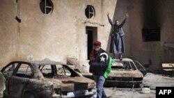 Một người biểu tình đứng trên chiếc xe bị đốt cháy trong trụ sở cảnh sát