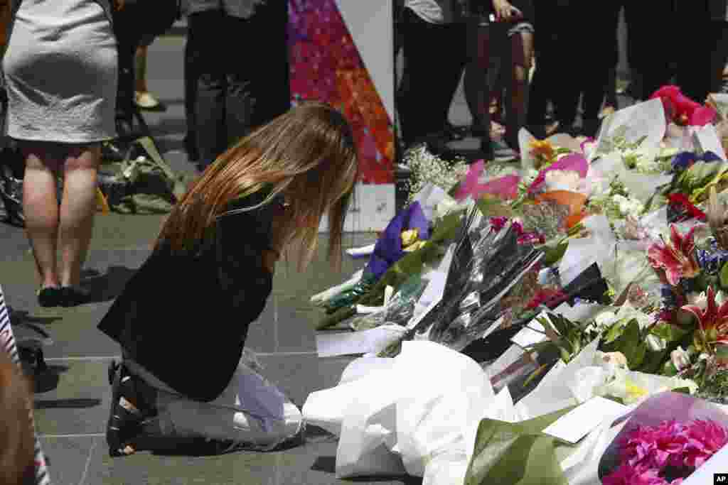 A woman kneels as she lays flowers in a makeshift memorial near the site where a gunman held hostages for 16 hours at a popular Sydney cafe, Australia, Tuesday, Dec. 16, 2014.