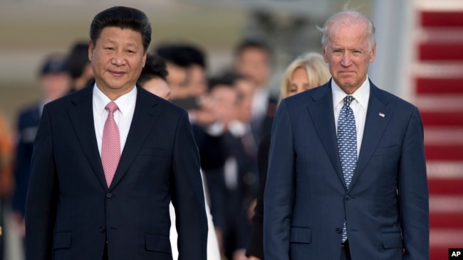 Chinese President Xi Jinping and Vice President Joe Biden walk down the red carpet on the tarmac during an arrival ceremony in Andrews Air Force Base, Md., Thursday, Sept. 24, 2015.