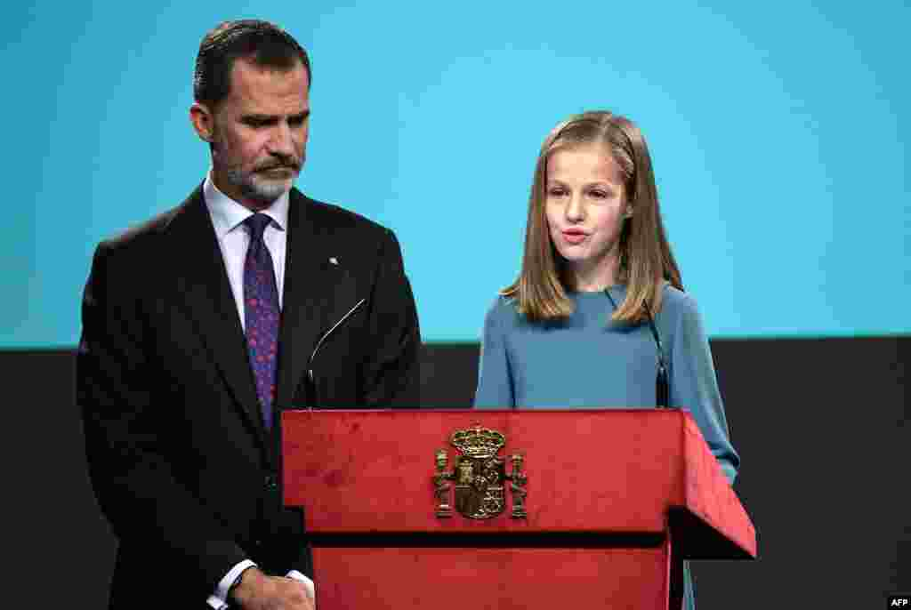 Spanish heiress of the throne, princess Leonor (R), reads the Spanish Constitution next to her father, King Felipe VI, during a ceremony marking 40 years of the constitution's approval by the parliament, at the Cervantes Institute in Madrid.