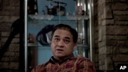 In this Feb. 4, 2013 photo, Ilham Tohti, an outspoken scholar of China's Turkic Uighur ethnic minority, pauses during an interview at his home in Beijing, China.