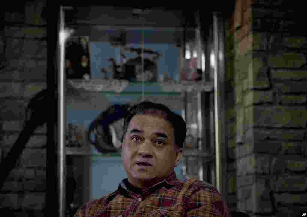 In this Feb. 4, 2013 photo, Ilham Tohti, an outspoken scholar of China's Turkic Uighur ethnic minority, pauses during an interview at his home in Beijing, China. Tohti was set to go on trial on separatism charges on Sept. 17, 2014.