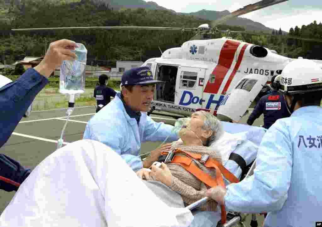 Một phụ nữ cao tuổi được khiêng trên một chiếc cáng để được trực thăng chở tới bệnh viện ở Yame, tây nam Nhật Bản, ngày 16/7/2012