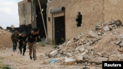 Free Syrian Army fighters run with their weapons during clashes with forces loyal to Syria's President Bashar al-Assad at the Karam Barre front line in Aleppo, Nov. 2, 2014.