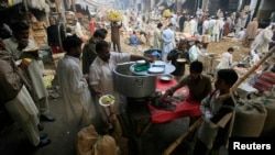 A man sells food at a fruit and vegetables market in Lahore November 12, 2012. REUTERS/Mani Rana (PAKISTAN - Tags: SOCIETY BUSINESS AGRICULTURE FOOD) - RTR3AB6X